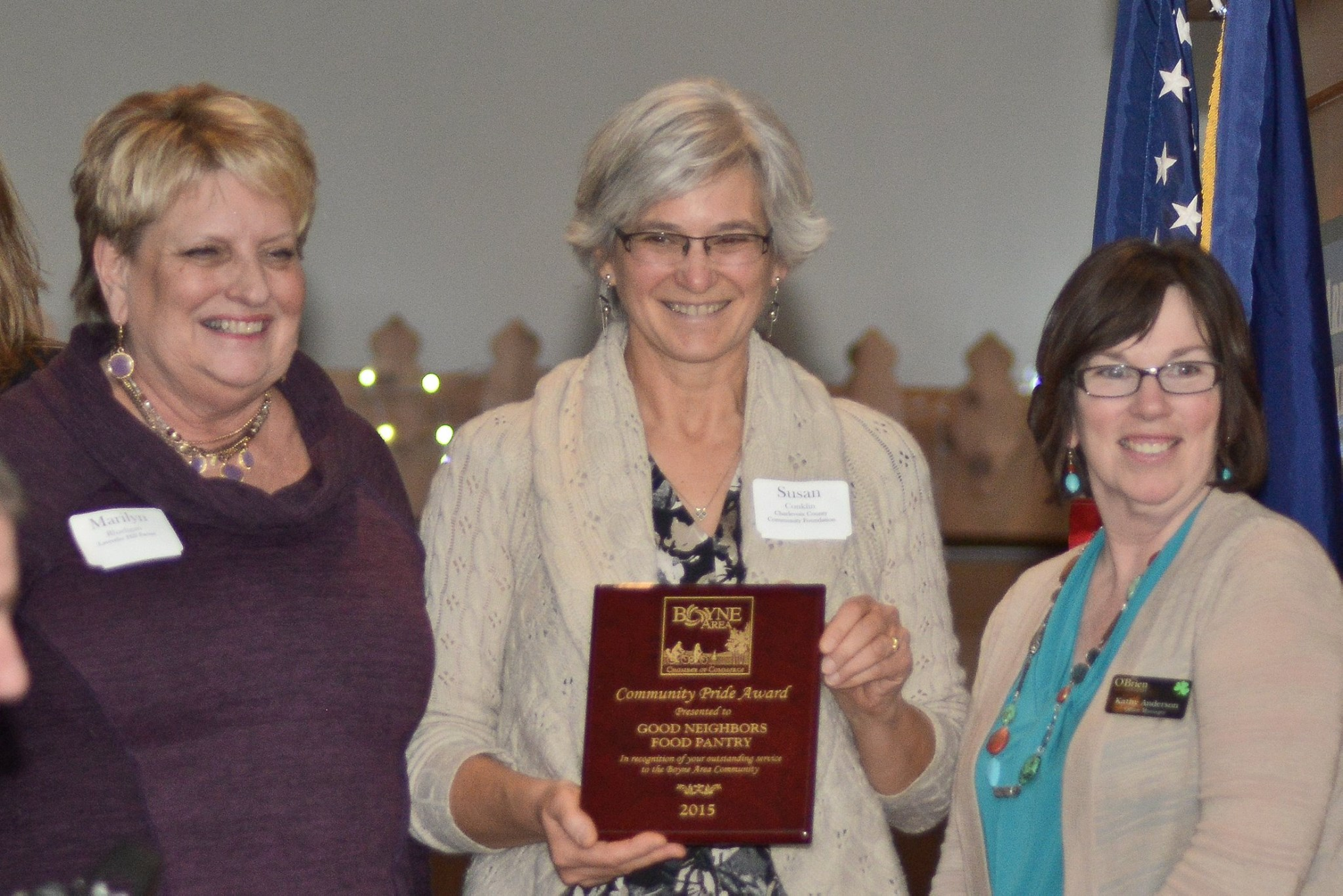 Three women holding Community Pride Award